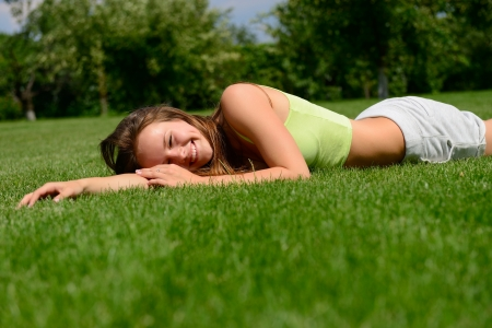 lying on grass: Cheeful young girl resting on summer green grass