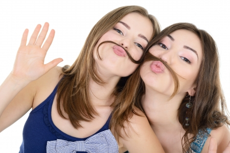 funny hair: Portrait of a two teen girls have fun and make faces with moustache made of hair pigtail, isolated on white