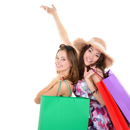 Beautiful happy young women with colored shopping sale bags in summer clothes pointing with hands up into the copyspace over white  photo