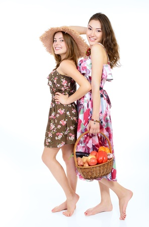two young beautiful cheerful friends women holding baskets with vegetables and fruits ready for summer picnic photo