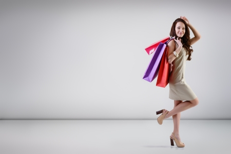 Beautiful young fashion woman posing at studio with shopping bags, full length portrait photo