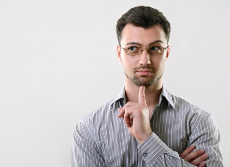 Young handsome thoughtful business man has idea, studio over gray background photo