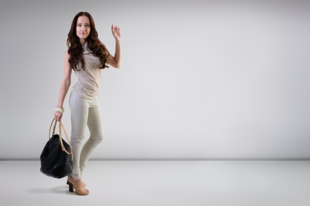 Beautiful young fashion woman posing at studio with bag, full length portrait photo