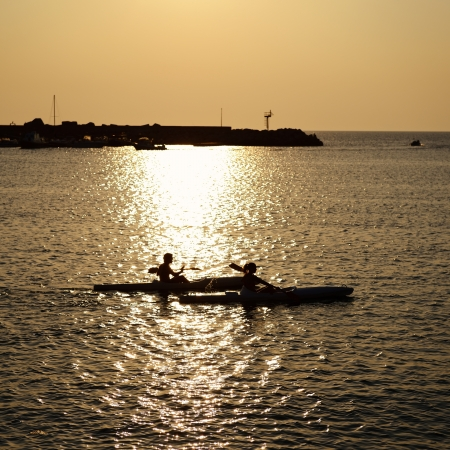 couple paddle together in sumertime evening sea photo