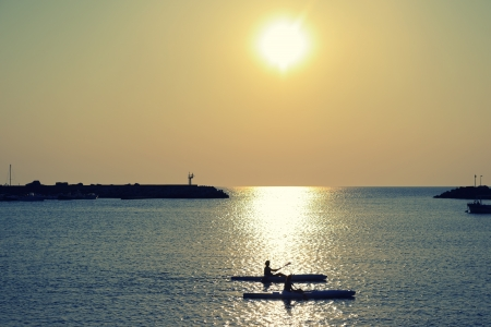 couple paddle together in sumertime evening sea over sunset photo