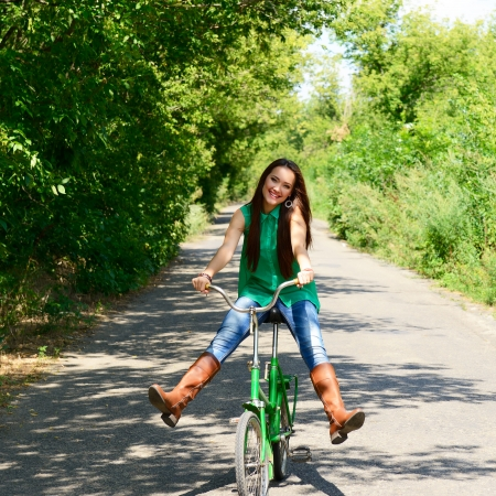excited young beautiful woman happy riding in retro bicycle, summer outdoor photo