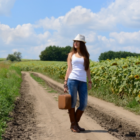 young woman with retro suitcase traveling in countryside, summer nature outdoor photo