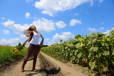 beautiful happy girl dancing with sunflowers in summer countryside photo