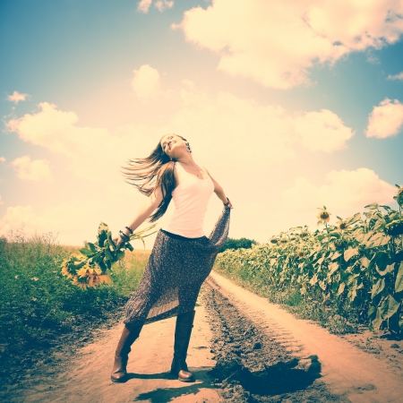 beautiful happy girl dancing with sunflowers in summer countryside, toned photo