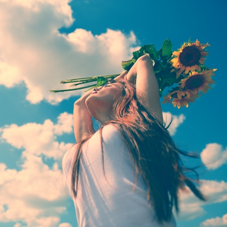 young beautiful woman enjoying summer, youth and freedom, holding sunflowers above head, against blue sky, toned image photo