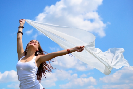 Happy young woman holding white scarf with opened arms expressing freedom, outdoor shot against blue sky photo