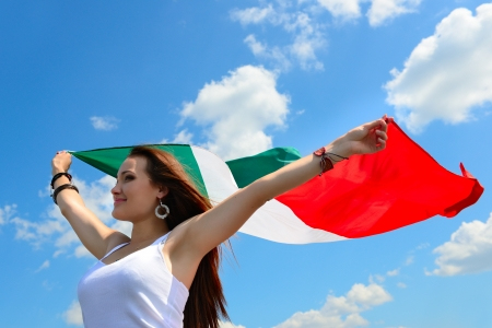 young beautiful cheerful woman holding italian flag against summer blue sky, with love to homeland photo