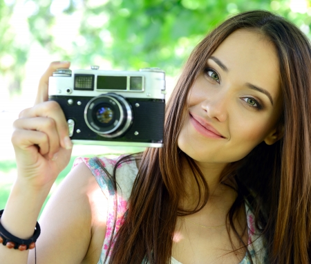 Cheerful beautiful girl talking pictures with vintage camera in summer park photo