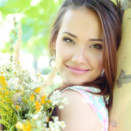 pretty lady: young beautiful lady with field flowers outdoor portrait, charming girl resting in summer park, toned and noise added