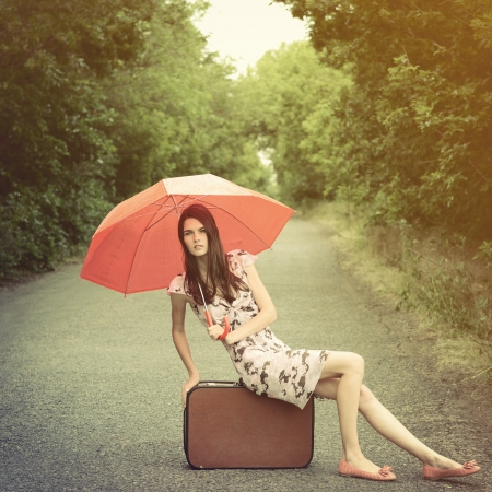 Attractive young woman hitchhiking along a road, toned, vintage stylization photo