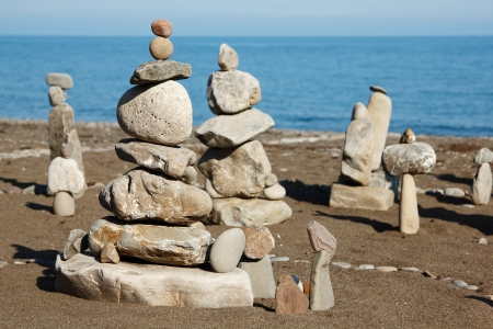 Pebble Beach: balanced stones, pebbles stacks against blue sea Stock Photo