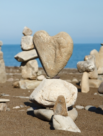 group of balanced stones with rocks heart at front view, pebbles stacks against blue sea photo