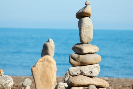 balanced stones, pebbles stacks against blue sea photo