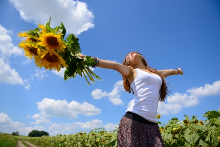 young beautiful woman enjoying summer, youth and freedom, holding sunflowers above head, against blue sky photo