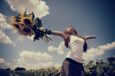 young beautiful woman enjoying summer, youth and freedom, holding sunflowers above head against blue sky, for vintage stylization image toned and noise added Stock Photo