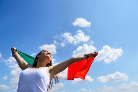 homeland: young beautiful cheerful woman holding italian flag against summer blue sky, with love to homeland