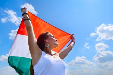 bandera italiana: joven y bella mujer alegre celebración de la bandera italiana contra el cielo azul del verano, con el amor a la patria