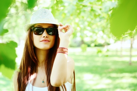 young woman walking in summer park  in sunglasses and fedora with long brown hair