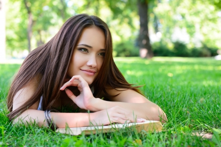 beautiful girl reading book in the summer park  photo