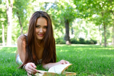 lying on grass: beautiful girl reading book in the summer park