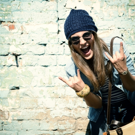beautiful girl face: portrait of beautiful cool girl gesturing in hat and sunglasses over grunge wall