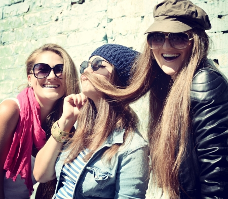 Girls having fun together outdoors and making moustache of hair, lifestyle theme,toned  photo