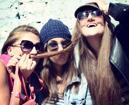 Girls having fun together outdoors and making moustache of hair, lifestyle theme, toned image photo