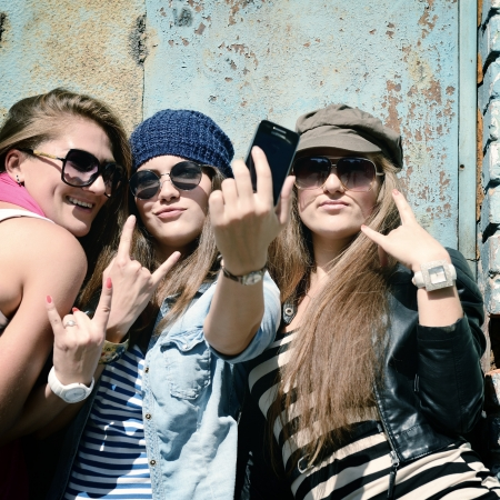 Girls having fun together outdoors and making photo with smart phone, lifestyle, toned and noise added photo