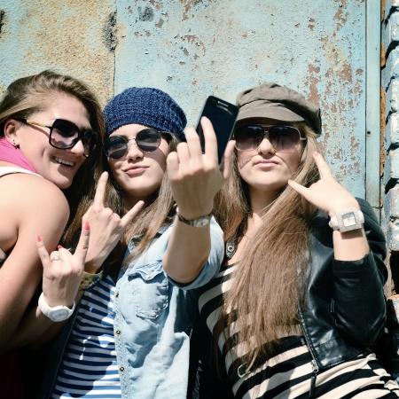 chicas divirtiendose: Muchachas que se divierten juntos al aire libre y hacer fotos con el tel�fono elegante, forma de vida, tonificada y el ruido a�adido