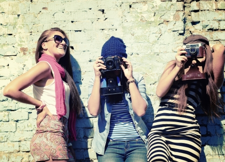 cool girl: urban girls have fun with vintage photo cameras outdoor near grunge wall