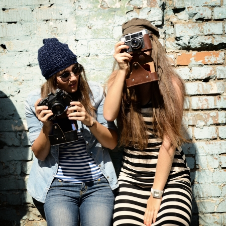 cool: urban girls have fun with vintage photo cameras outdoor near grunge wall