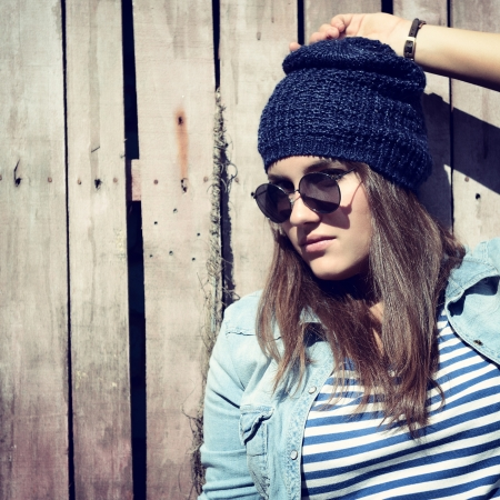 beautiful cool girl in hat and sunglasses against grunge wooden fence photo