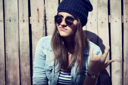 portrait of beautiful cool girl gesturing in hat and sunglasses photo