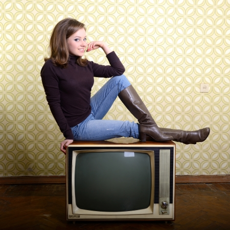 vintage art portrait of young smiling woman sitting on retro tv set looking out at camera in room with wallpaper