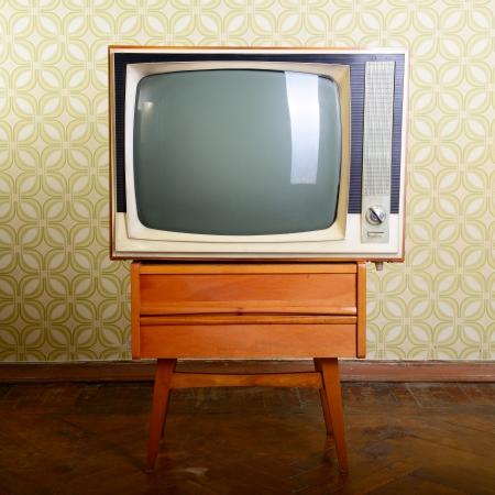 retro tv met houten kist in de kamer met vintage wallper en parket