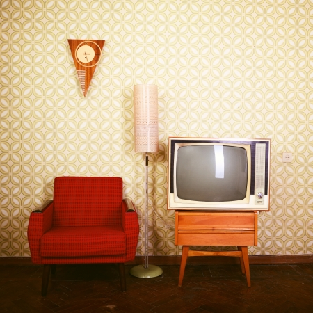 Vintage room with wallpaper, old fashioned armchair, retro tv, phone, clocks, radio player and standart lamp, toned photo
