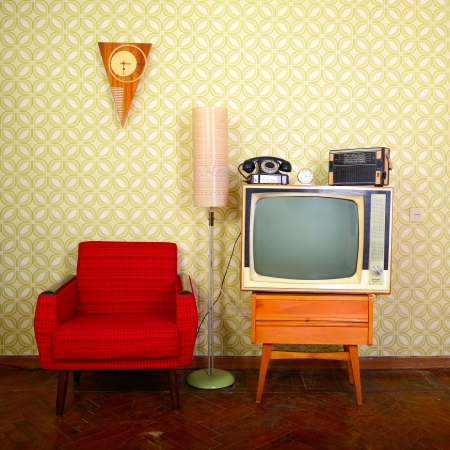 styled interior: Vintage room with wallpaper, old fashioned armchair, retro tv, phone, clocks, radio player and standart lamp