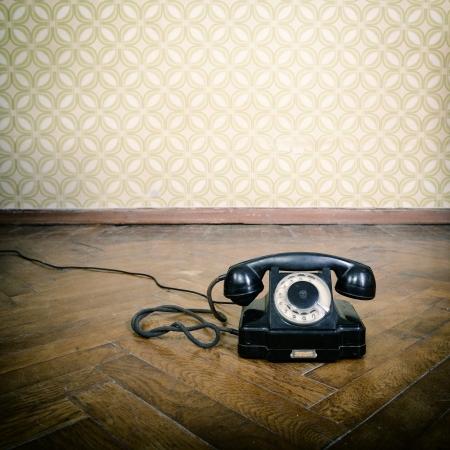 retro telephone: vintage old telephone, black retro phone is on the floor of used parquet