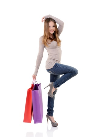beautiful happy teen girl shopaholic with colored shopping bags, full length portrait over white
