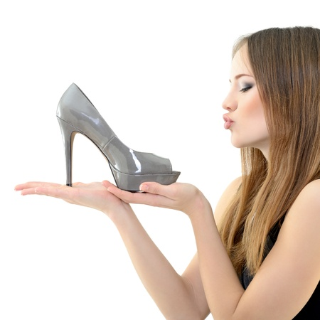 high heel shoes: girl holding shoe in hand an looking with love on it, over white Stock Photo