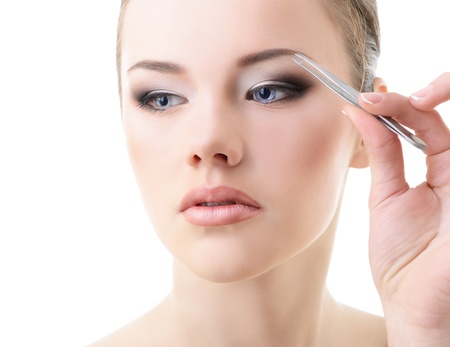plucking: Beautiful girl plucking eyebrows with tweezers over white Stock Photo