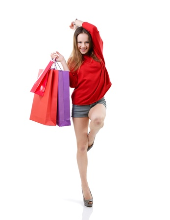 beautiful happy teen girl shopaholic with colored shopping bags, full length portrait over white photo