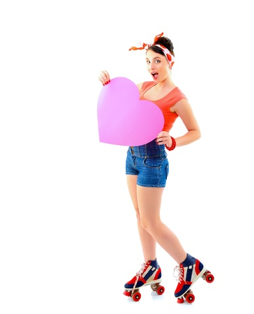 Pinup girl in retro roller skates holding big pink heart, full length portrait of young happy sexy woman in pin-up style in love, vintage stylization over white Stock Photo - 22279020