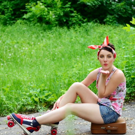 Pinup girl sitting on suitcase with retro roller skates and give kisses, portrait of young happy sexy woman in pin-up style over park nature outdoor photo