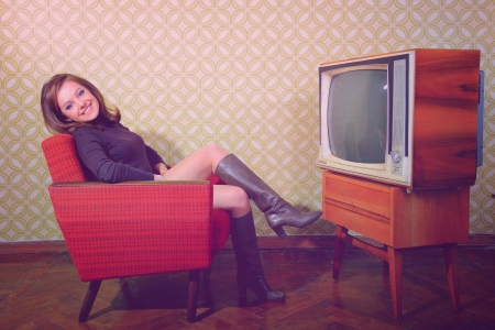portrait of young smiling woman sitting in vintage room and watching tv, retro stylization, toned and noise added photo
